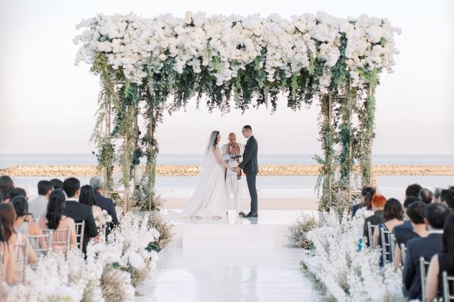 Bride and groom taking vows under a giant floral framwork with the beach and ocean behind