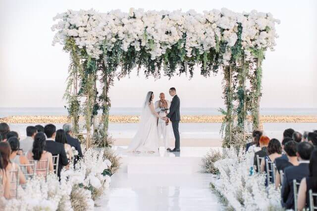 Bride and Groom taking vows under an oversized flowery wedding pergola on the oceanfront beach lawn in Apurva Kempinski resort
