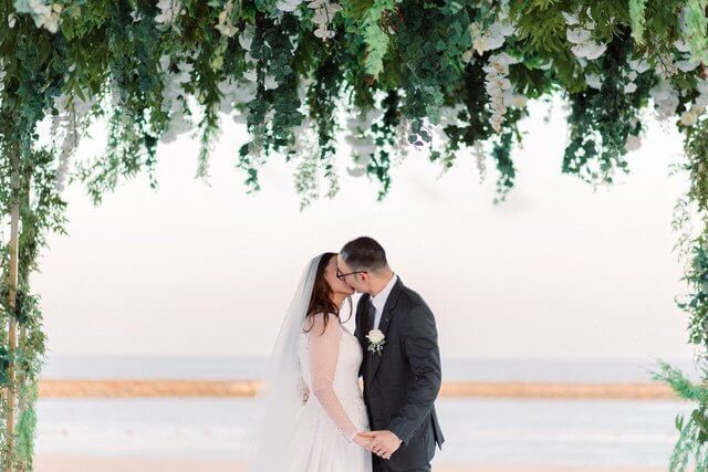 Bride and Groom kissing with ocean backdrop