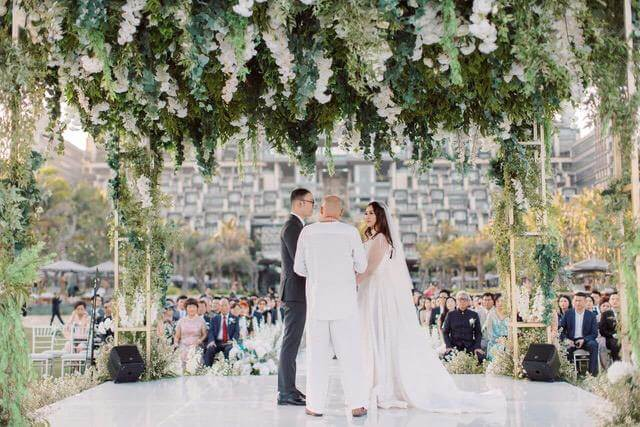 Bride and Groom taking vows with celebrant under flower pergola