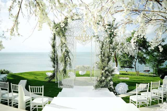 White iron pergola on grass stage surrounded by white chairs and white blossoming trees
