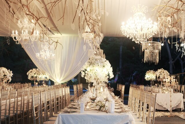 Long white tables with tall flower centerpieces inside marquee with hanging chandeliers