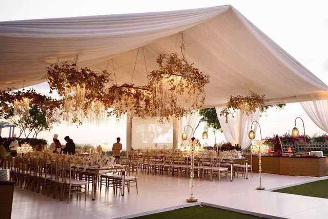 White open air marquee with hanging bronze floral chandeliers above dining set up