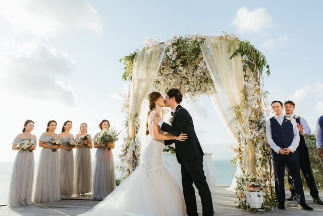 Brdie and groom kissing under a flower pergola with the bridal party and groomsmen on either side of them