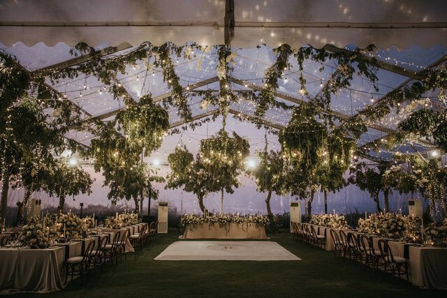 Large transparent wedding marquee with hanging leave chandeliers and fairy lights