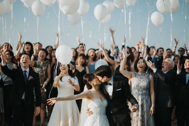 Bride and Groom kissing with wedding guests releasing white balloons