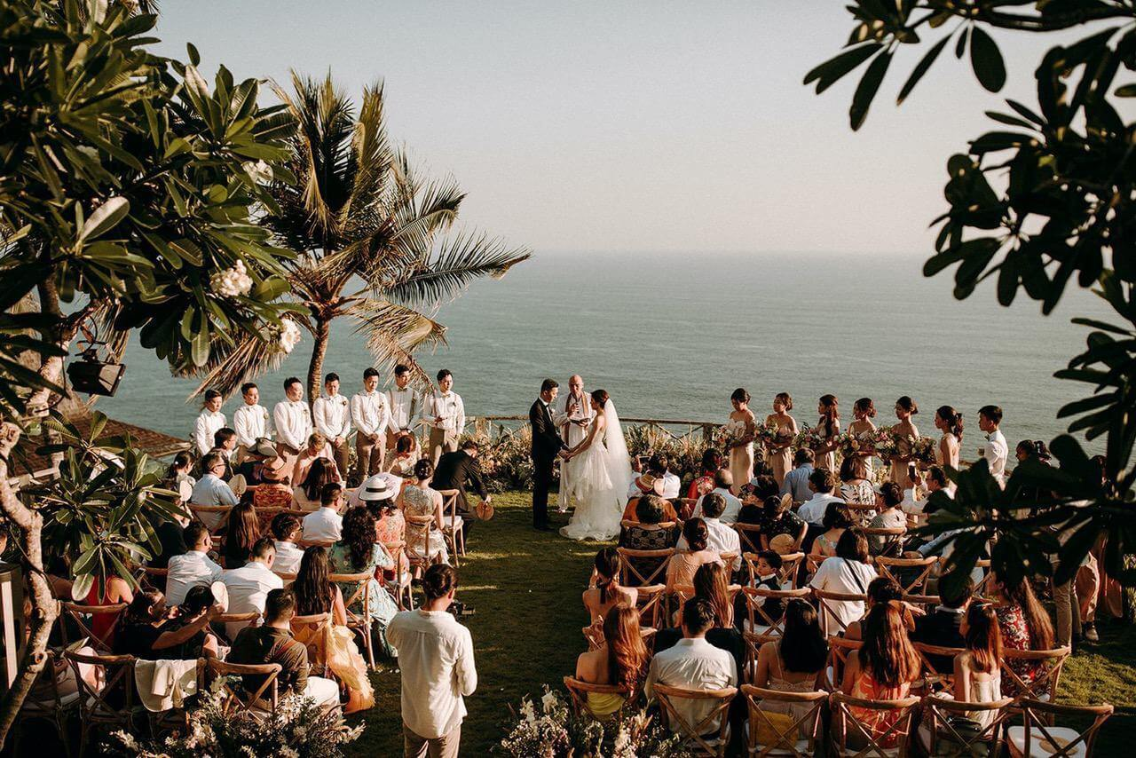 Bride and Groom taking vows with wedding guests in a Bali villa garden