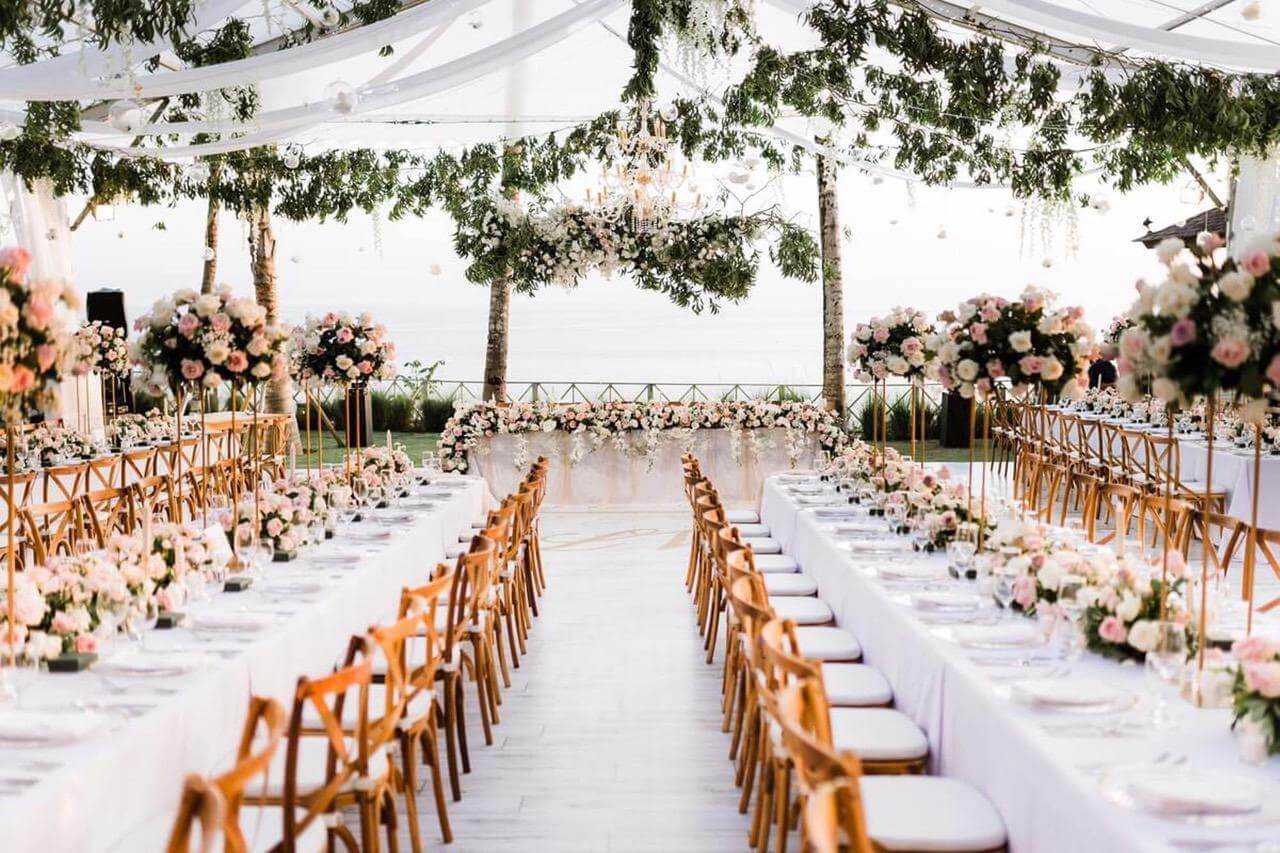 Spacious marquee with long tables with white tablecloth and wooden chairs