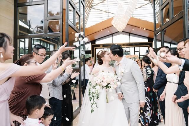Bride and Groom kissing with guests throwing flower petals