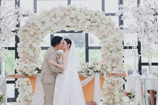 Bride and Groom kissing under a white flowery wedding arch