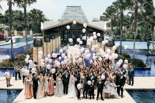 Wedding guests releasing pink baloons outside of Eternity chapel