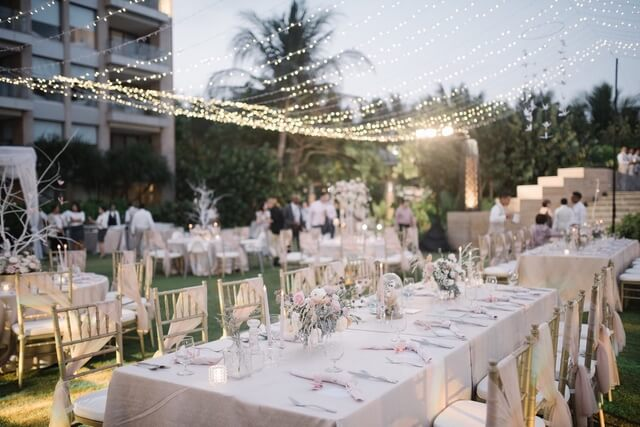 Long tables set for dinner with fairy lights hanging from above