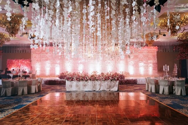 Dance floor at wedding reception illuminated pink with hanging white flowers from ceiling