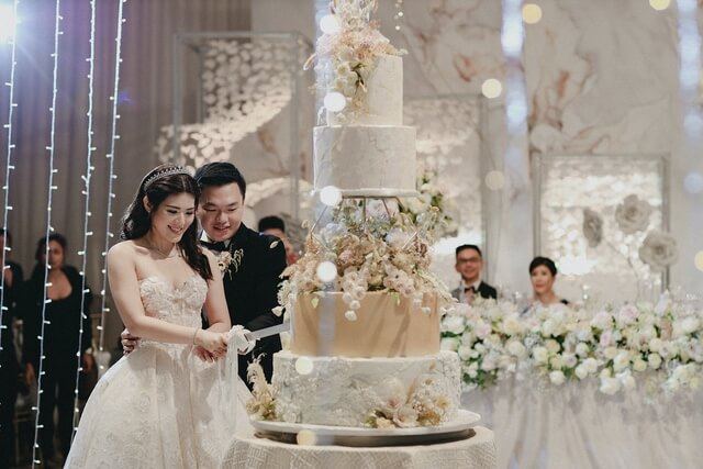 Bride and Groom cutting 5 tiered wedding cake adorned with dried flowers