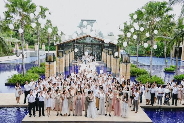 Wedding guests releasing white balloons in front of Mulia Resort's Eternity chapel