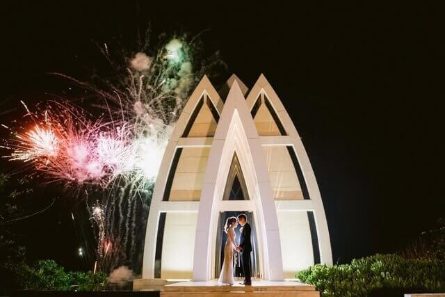 Bride and Groom holding hands in front of Ritz Carlton's Majestic chapel with fireworks exploding behind