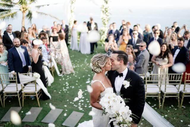 Bride and Groom kissing in front of wedding guests in Khayangan Estates wedidng garden